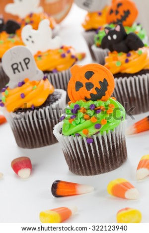 Halloween cupcake with jack·tern and bat decorations surrounded by Halloween cupcakes, corn candies, and decoration.