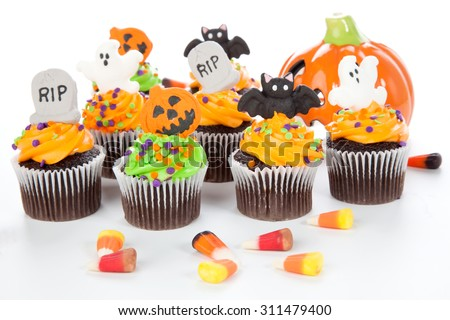 Halloween cupcake with RIP, ghost, bat, and  jack-o'-lan�·tern decorations surrounded by Halloween cupcakes, corn candies, and decoration. - stock photo