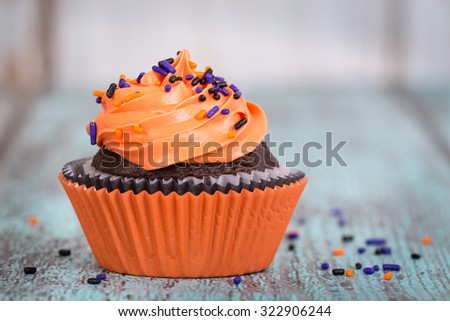Halloween cupcake with sprinkles on vintage wooden background