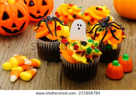 Halloween cupcakes and candy on wooden table - stock photo