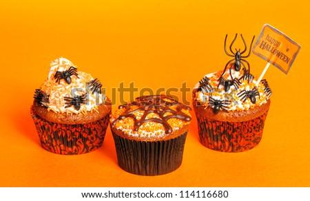 Halloween cupcakes with decoration over orange background - stock photo