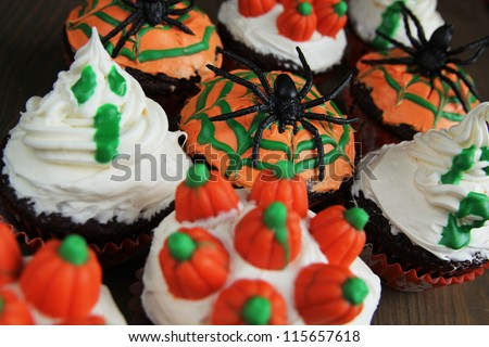 Halloween cupcakes with ghost, spider and pumpkins - stock photo