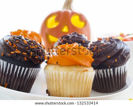 Halloween cupcakes with orange and black icing on white plate. - stock photo