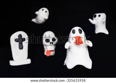 Halloween cute ghost, skull and tombstone made out of play dough against black background