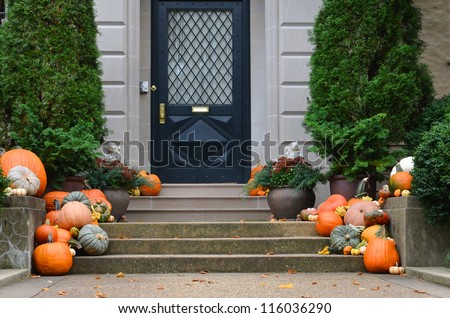 Halloween decorated front door with various size and shape pumpkins - stock photo