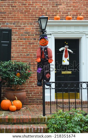 Halloween decorated front door with various size and shape pumpkins and scary puppets  - stock photo