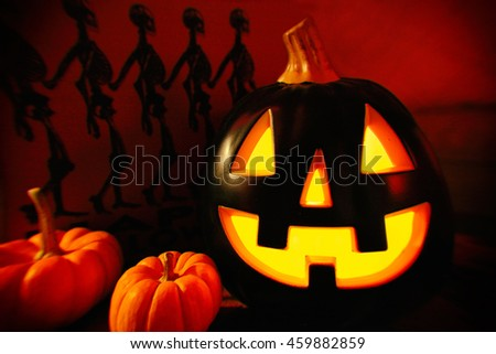 halloween decorations jack o lantern with small pumpkins and skeleton background