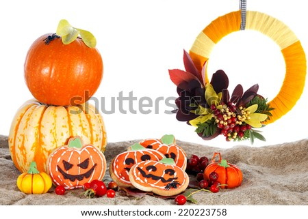 Halloween decorative cookies, wreath and pumpkins as popular American event party dessert idea. Isolated on white background