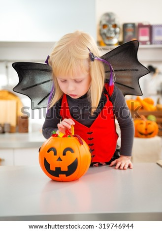 Halloween dressed girl with pumpkin bucket full of candy in decorated kitchen.  Halloween Candy is so good. Traditional autumn holiday - stock photo