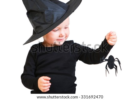 Halloween dressed toddler girl in black  little witch costume looking to small spider - stock photo