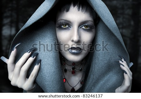 Halloween. Fashion portrait of witch or night vampire woman. Dark gothic makeup