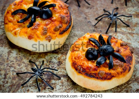 halloween food background funny mini pizza with olive spider decoration