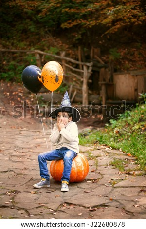 Halloween. Frightened boy in cap vedby sits on a large pumpkin. - stock photo