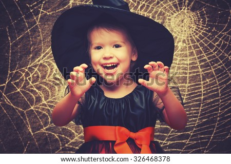 Halloween. funny little witch on a dark background - stock photo