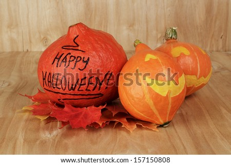halloween funny pumpkins, on wood table with leaves
