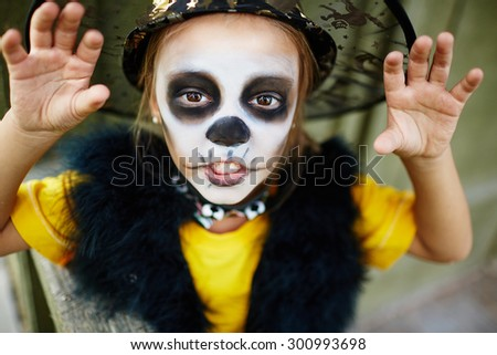 Halloween girl with painted face and frightening pose looking at camera - stock photo