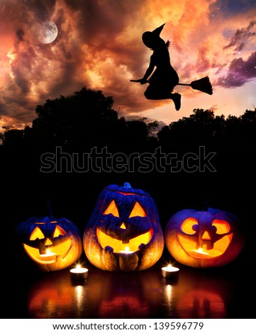 Halloween glowing pumpkins on the table and witch silhouette flying at dramatic night sky with moon