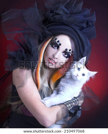 Halloween: Gothic lady with artistic makeup posing witt white cat - stock photo