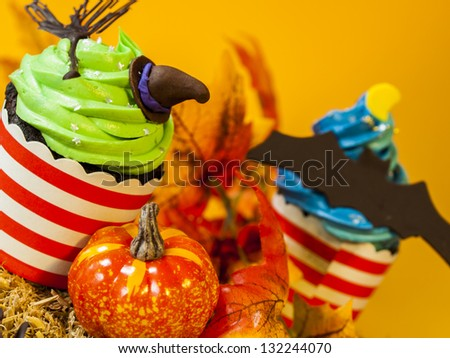 Halloween gourmet cupcakes with holiday decor orange background. - stock photo
