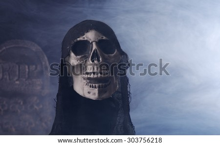 Halloween grim reaper prop on a smoky background - stock photo