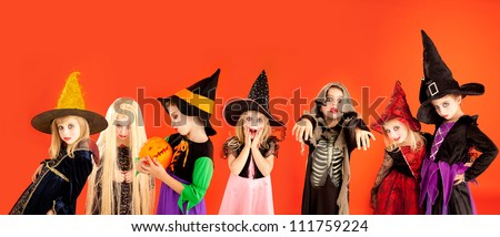 Halloween group of children girls costumes on orange background - stock photo