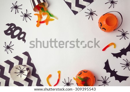 Halloween holiday background with spiders and candy. View from above