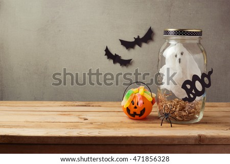 Halloween holiday decoration with ghost in jar and candy on wooden table