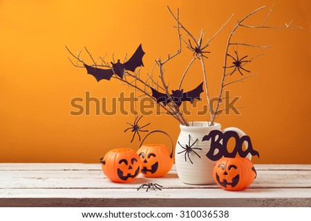 Halloween home decorations with spiders and pumpkin bucket for trick or treat - stock photo