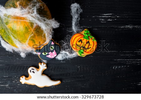 Halloween homemade gingerbread cookies and pumpkin with with spiderweb background