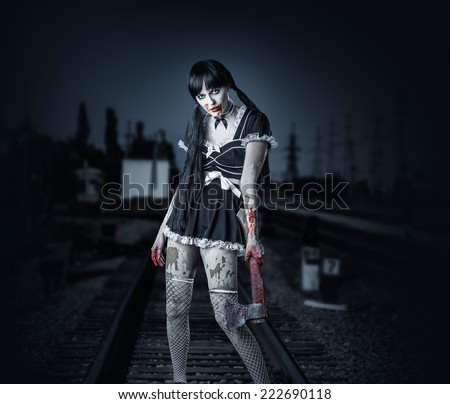 Halloween horror. Dirty woman  holding bloody ax in hand outdoor  - stock photo
