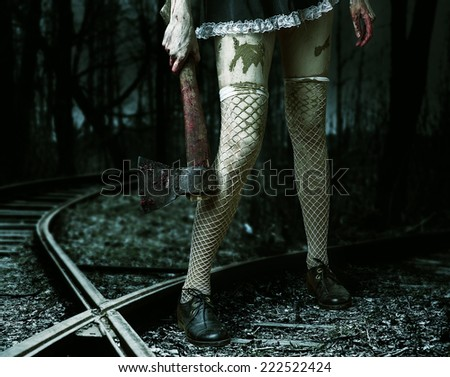 Halloween horror. Dirty woman's hand holding a bloody ax outdoor in forest - stock photo