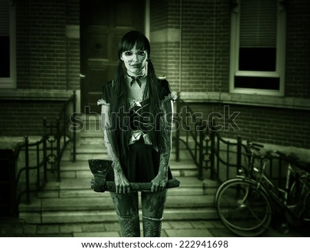 Halloween horror. Scary woman ghost with ax on porch of house - stock photo