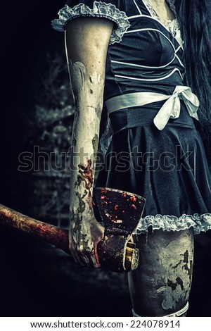 Halloween horror. Scary zombie woman holding bloody axe in dirty hand - stock photo