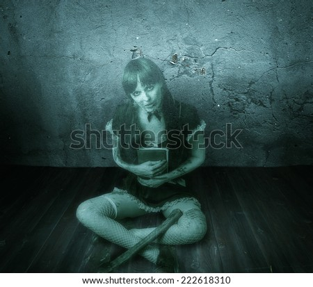 Halloween horror. Transparent blured woman holding book and a bloody ax sitting on a wooden floor in abandoned house - stock photo