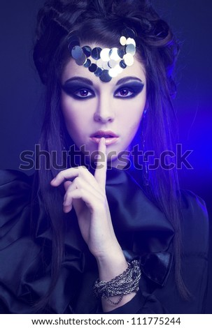 Halloween image. Young stylish woman in black dress with artistic visage standing  in blue light. - stock photo