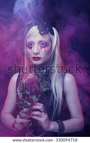 Halloween image. Young woman in black dress and with bloody tears.