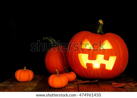 Halloween Jack o Lantern night scene with pumpkins on wood with black background
