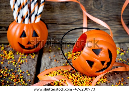 Halloween Jack o Lantern pail on a wooden table with orange ribbons. Halloween party decoration selective focus