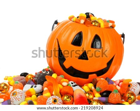 Halloween Jack o Lantern pail overflowing with candy - stock photo