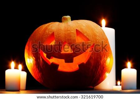 Halloween Jack O' Lantern pumpkin and candles on black background - stock photo