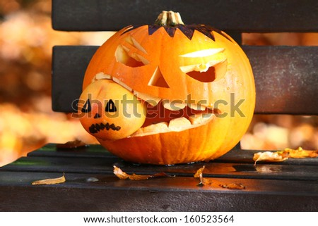 Halloween Jack-o-lantern sat on park bench eating orange - stock photo