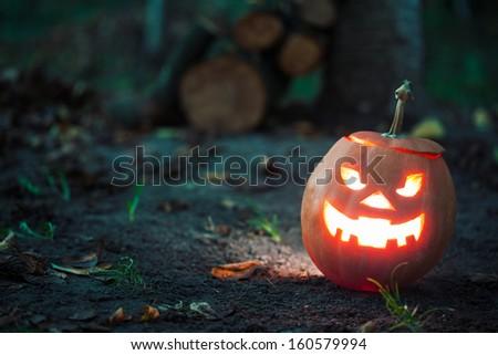 halloween jack-o-lantern standing on ground - stock photo