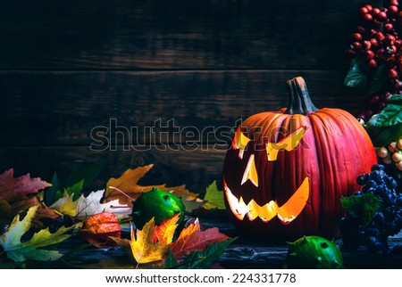 Halloween.Jack o lanterns Halloween pumpkin face on wooden background and autumn leaves - stock photo