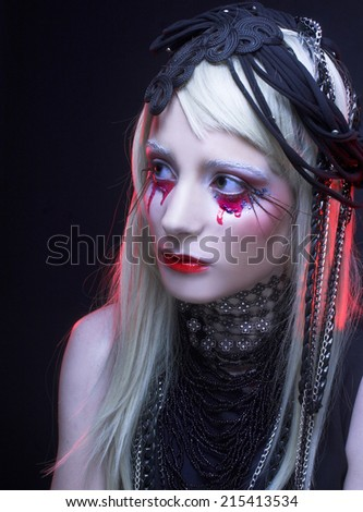 Halloween lady. Young woman in black dress and with bloody tears.