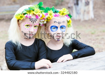 Halloween makeup. Photo of twin girls with black clothing sitting in front of a table outdoors - stock photo
