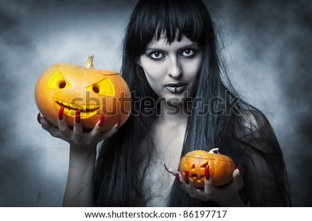 Halloween makeup. Sexy woman - Witch with long black hair and two pumpkins in hands smiling and look to shot