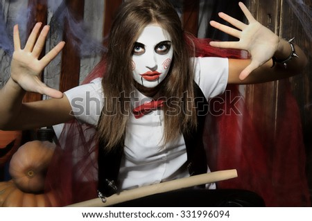 Halloween, mysticism, magic, mystery. Makeup in the style of Billy doll. Girl as a doll raises her arms showing open palms - stock photo