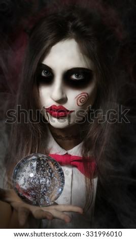 Halloween, mysticism, magic, mystery. Makeup in the style of Billy doll. Girl witch holding a magic transparent sphere. - stock photo