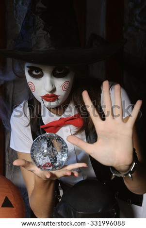 Halloween, mysticism, magic, mystery. Makeup in the style of Billy doll. The girl in a magic hat holding a ball - stock photo