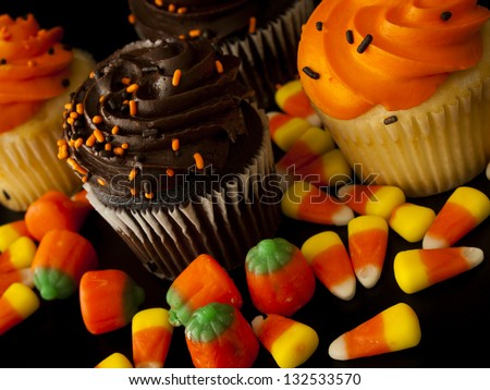 Halloween orange and black cupcakes with candy corn candies on black background.
